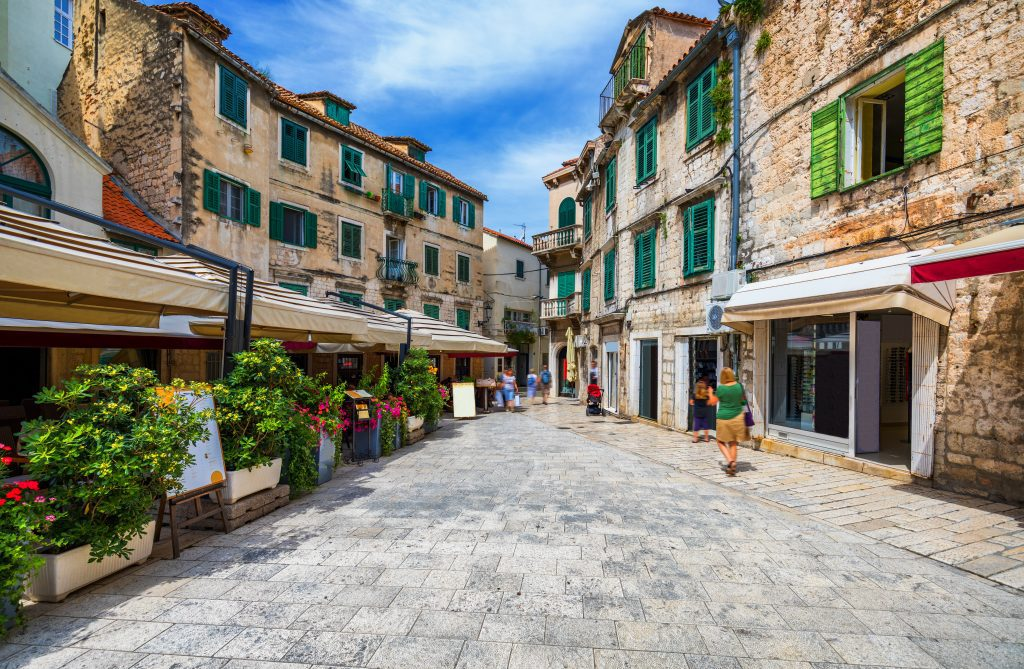 A street in Split's old town with stone buildings with emerald green shutters, and cafes surrounded with plants for privacy.
