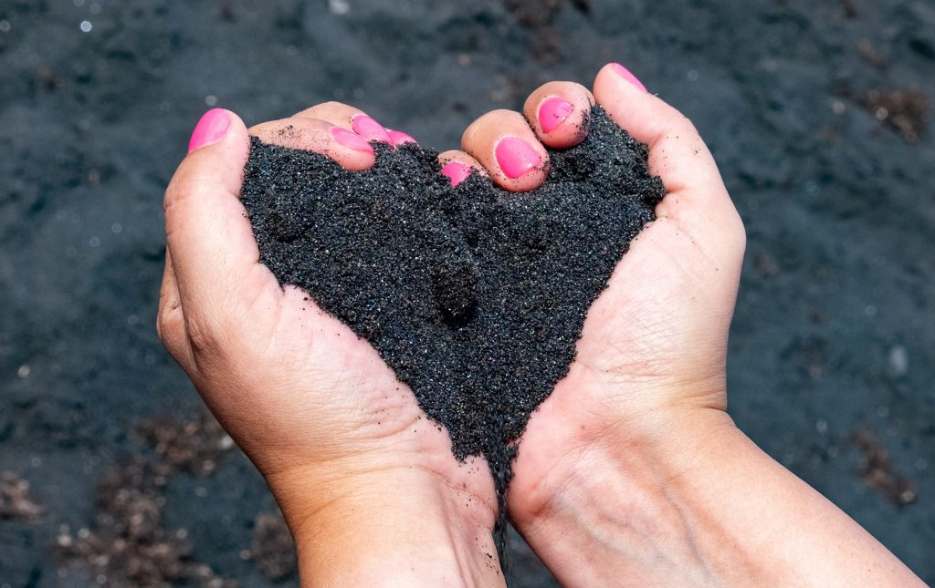 Kate's hands (with bright pink fingernails) holding a handful of sparkling black Stromboli sand, her hands forming the shape of a heart.