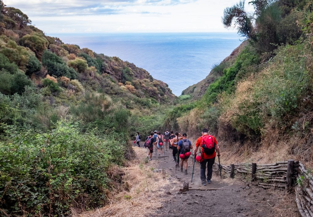 A group of hikers heading downhill with hiking poles, unused helmets dangling off their backpacks.