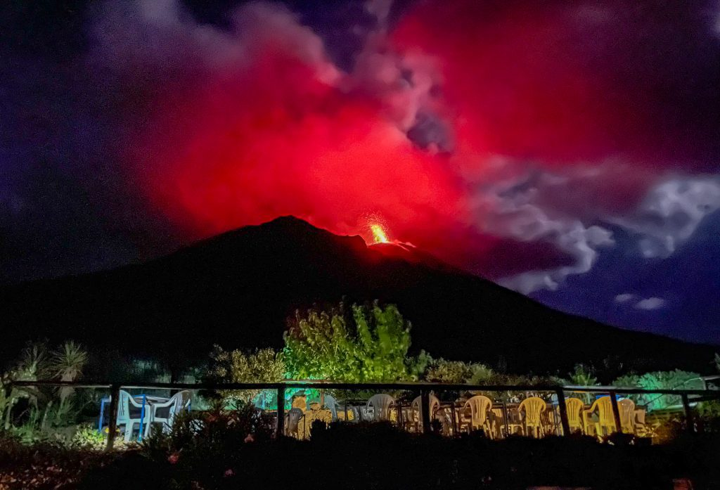 Stromboli's volcano as seen from Osservatorio, spewing out a plume of bright red lava against a dark indigo sky, looking even more ominous than before.