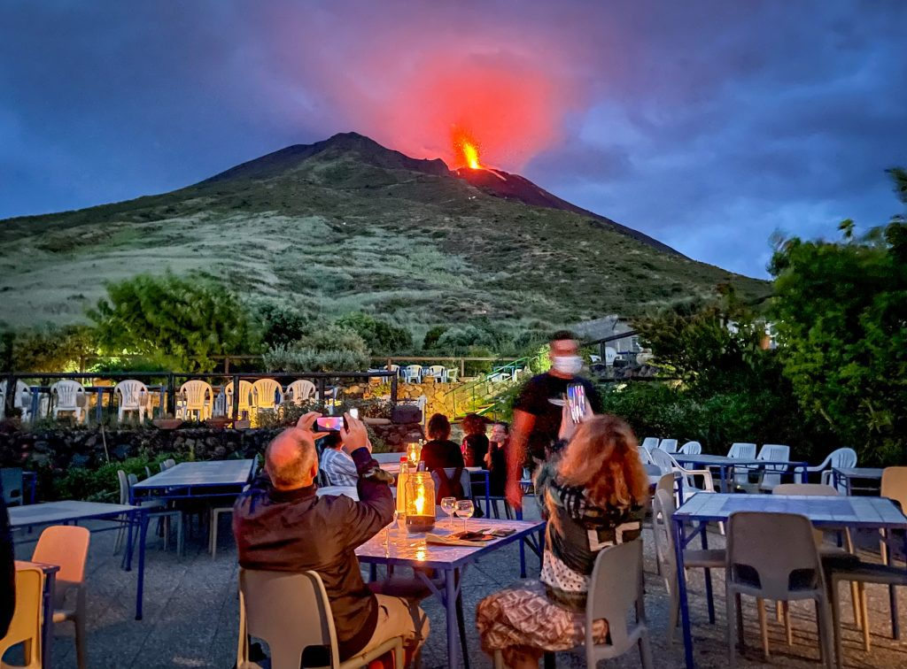 The view from Osservatorio on Stromboli: tables overlooking the volcano, which is exploding with a bright red plume of lava erupting from the top.