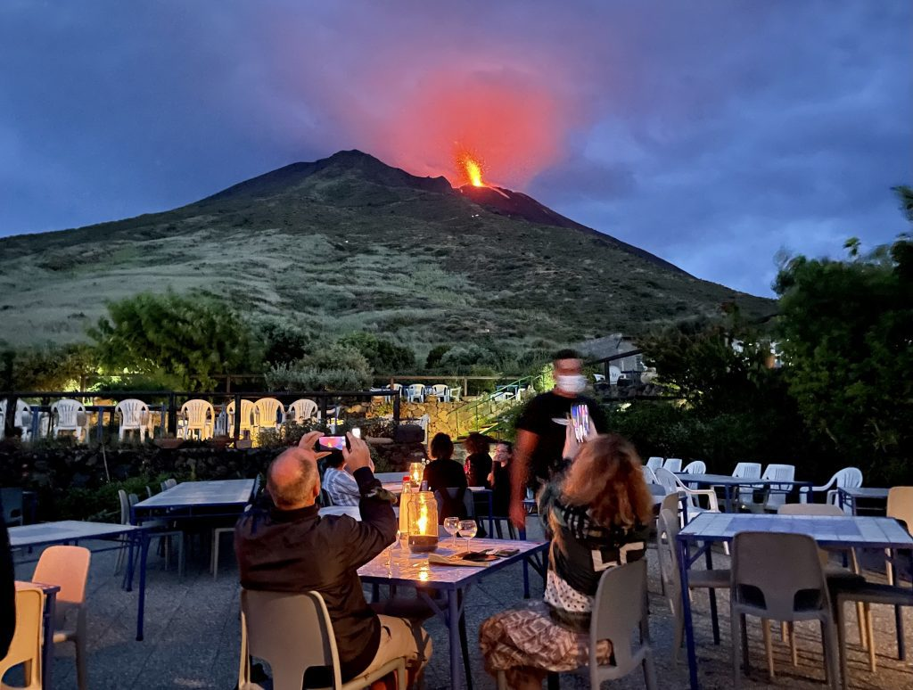 The volcano of Stromboli, spewing an explosion of bright red lava in a darkening sky. In the foreground, there are outdoor tables at Osservatorio restaurant and people have their phones out photographing the lava.
