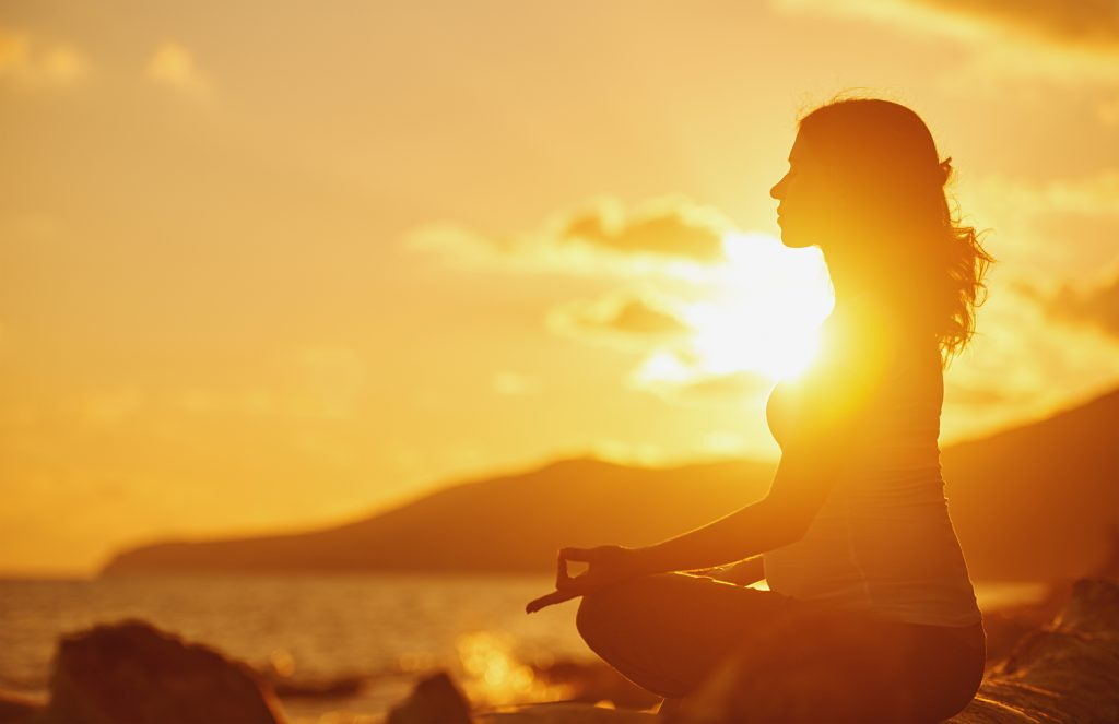 A woman doing yoga in lotus pose by the water in front of an orange sunset.