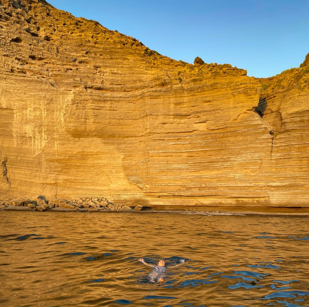 Kate swimming in the ocean, the bright orange lined cliffs of Pollara rising in the warm sunset light.