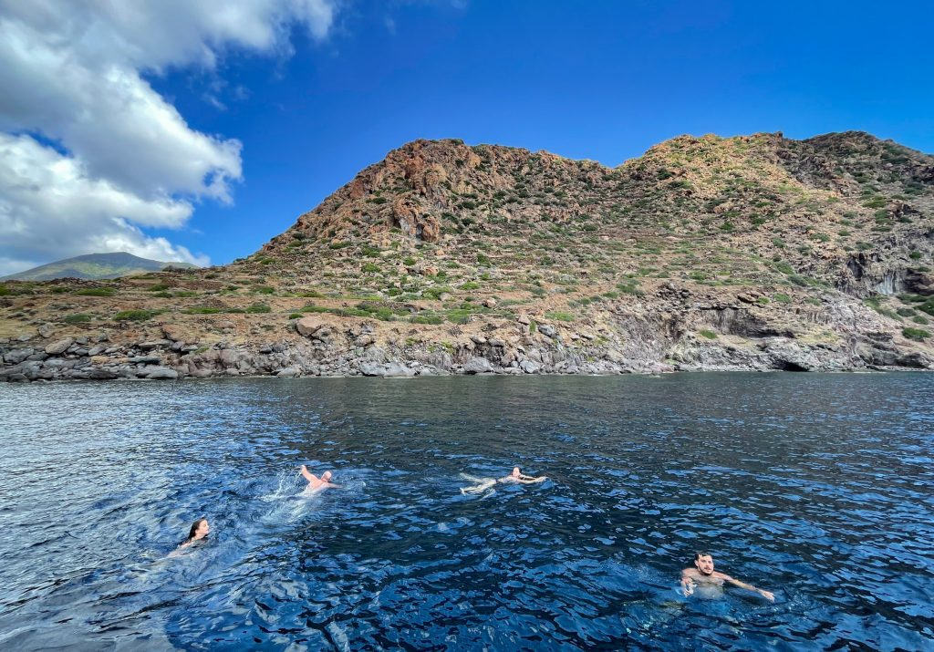 Four people swimming off the verdant coast of Filicudi.