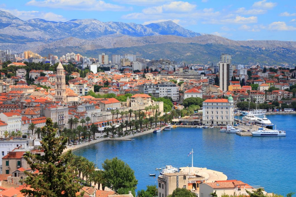 A view from above of Split, Croatia -- a city of stone buildings and orange roofs with one big church tower sticking out; in the background, some tall apartment buildings, then mountains.