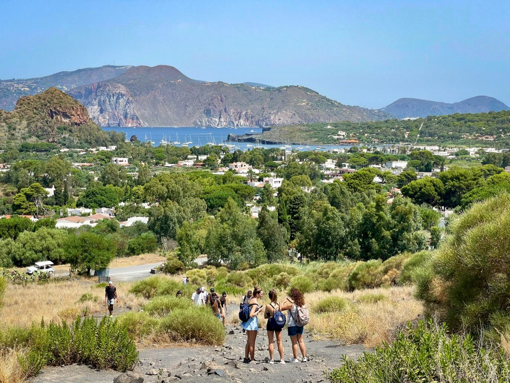 The view from the beginning of climbing Vulcano, with three teenage girls wearing backpacks and shorts having a conversation. In the background you see the green landscape, studded with white blocky homes, leading to the blue ocean, topped with white sailboats, and more islands in the distance.