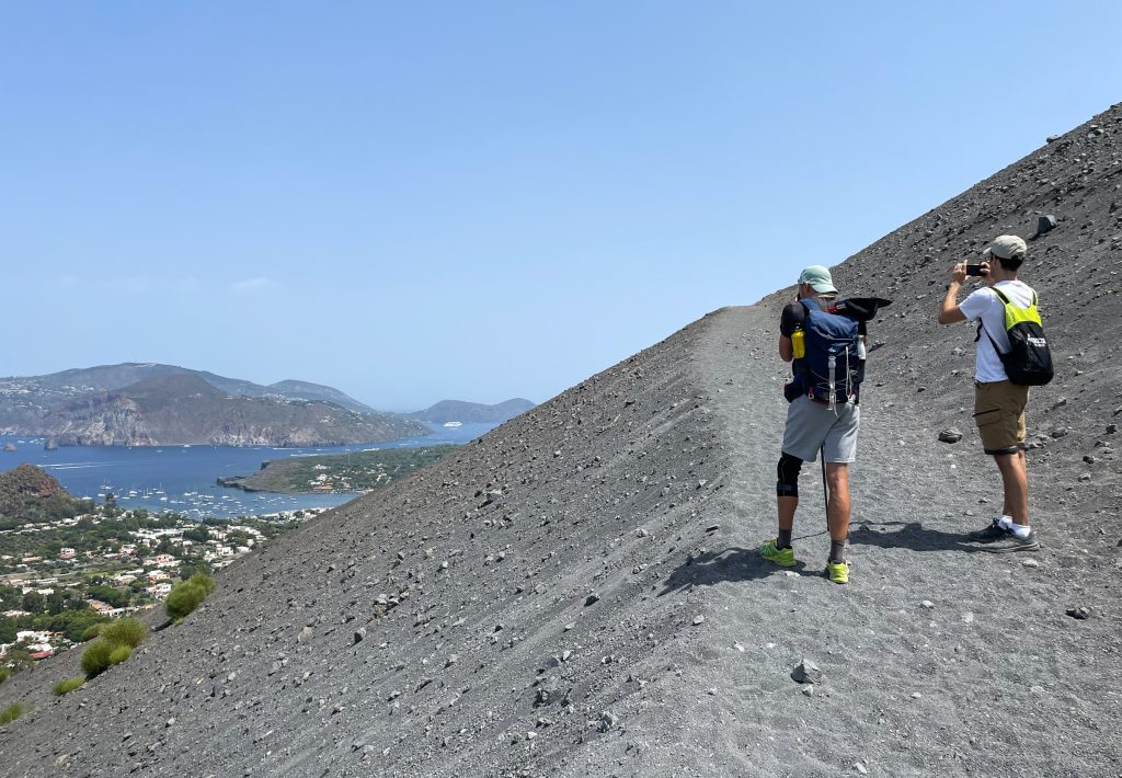 Two hikers taking photos of islands in the distance while climbing a sandy gray path on Vulcano.