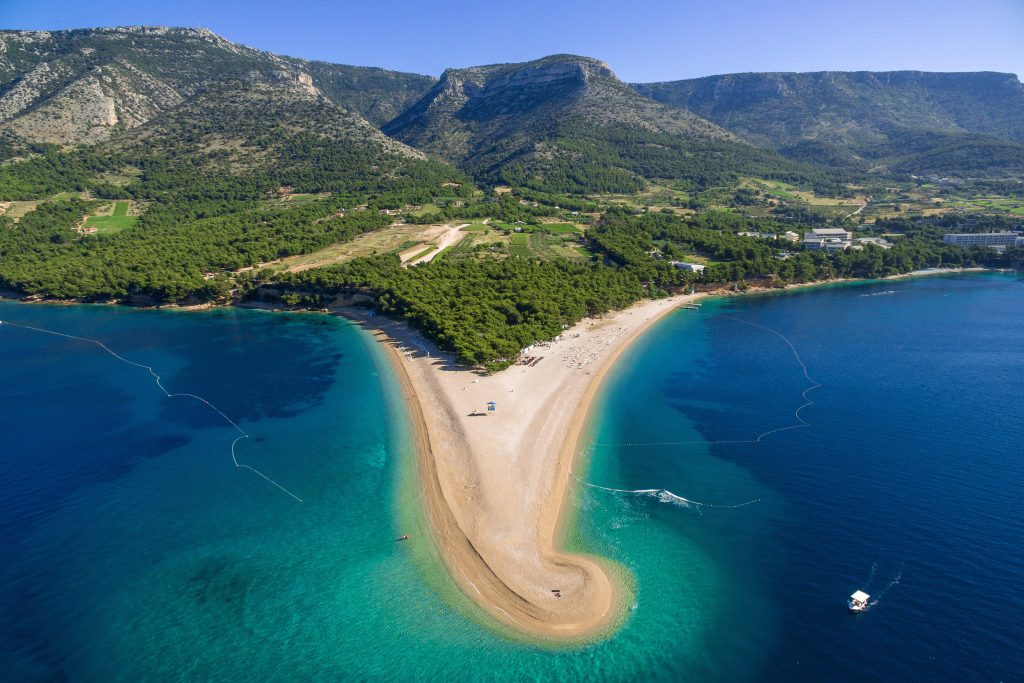 Zlatni Rat, the famous Golden Horn beach: A green forest island gives way to a long sandy horn-shaped beach, coming out from the island like a peninsula. It's not sandy in real life, it's all pebbles.