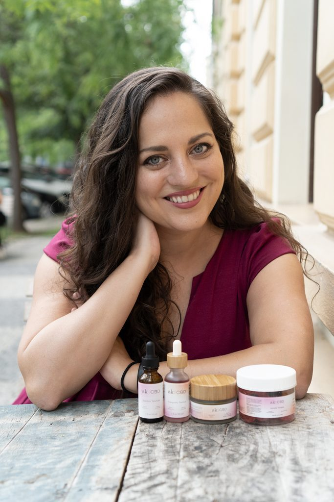 Kate sits at an outdoor cafe table and smiles at the camera, two bottles of AK CBD tinctures, one jar of soothing salve, and one jar of gummies in front of her.