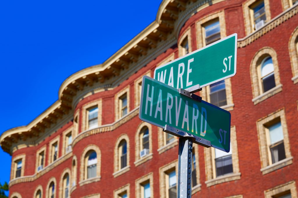 Two street signs reading Harvard St. and Ware St. in front of a red brick building.