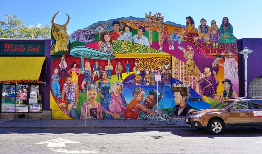 A brightly painted mural in Cambridge covered with people of all colors and sizes and backgrounds.