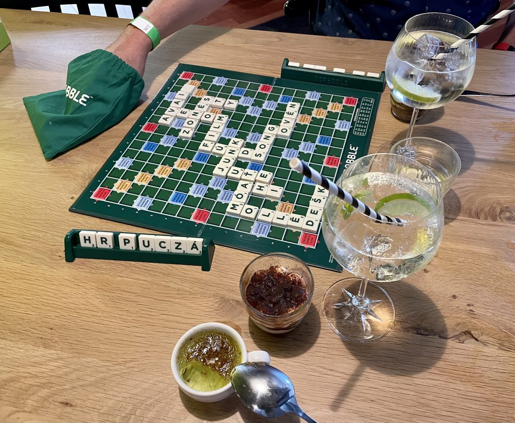 A Scrabble board that is clearly Czech with Czech letters, plus two cocktails, a pistachio creme brûlée, and tiramisu.