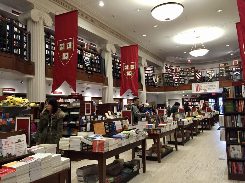 Harvard's bookstore. You see tables covered with paperbacks and tall red banners with the Harvard crest reading VERITAS, the school motto.