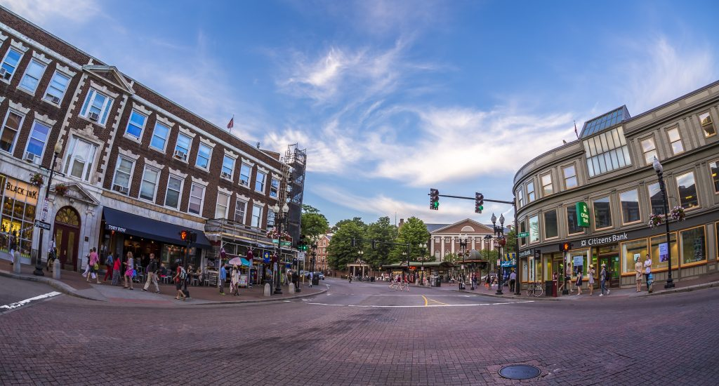 A wide angle shot of Harvard Square, stores and boutiques and banks in the buildings.
