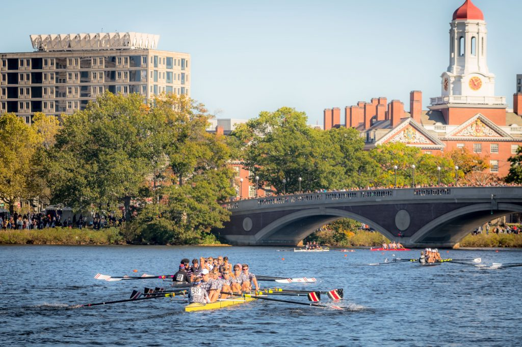 Several boats rowing crew along the Charles River; people standing on a bridge watch the race.