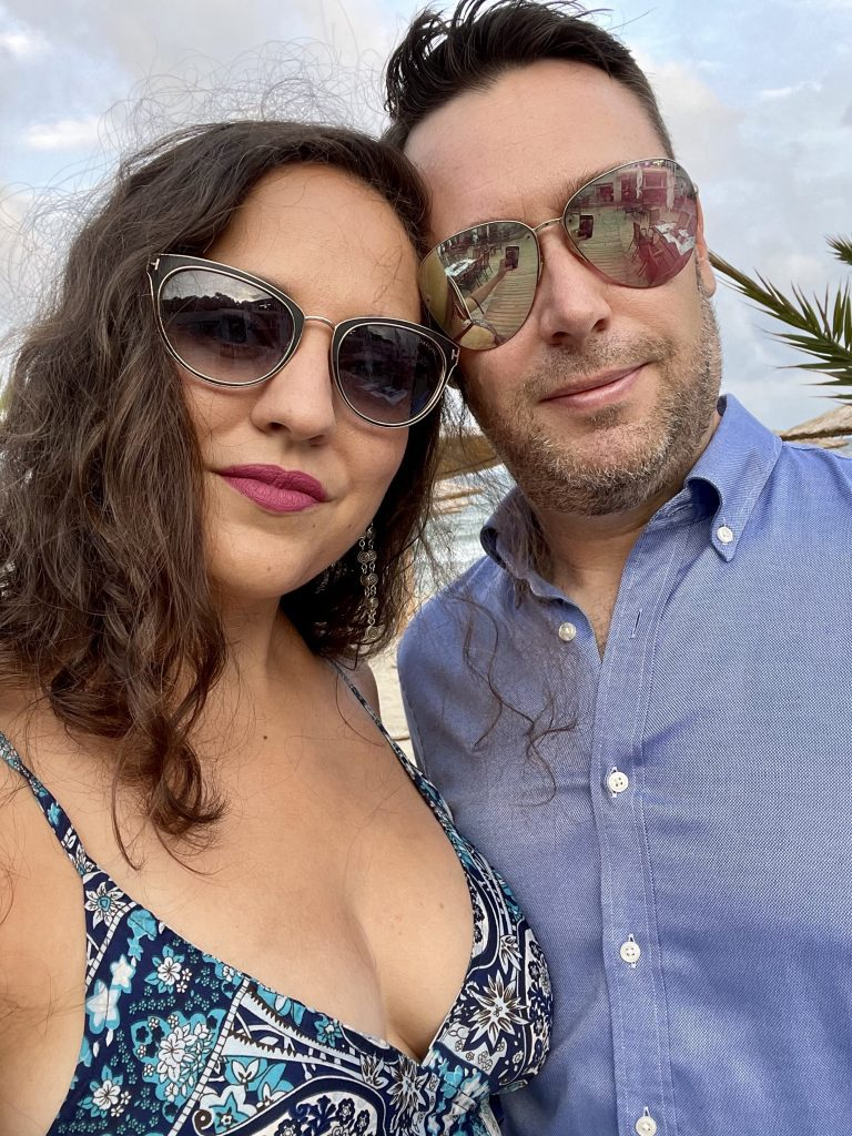 Kate and Charlie take a smoldering selfie, both wearing sunglasses and smiling gently. Kate's sunglasses, a gift from Charlie, are black and cat's eye shaped, outlined in gold, with the trademark gold T-shape of Tom Ford on the outer corners. Kate wears a low cut spaghetti strapped blue and white paisley patterned dress. Charlie wears reflective aviator sunglasses (surprise: they're actually Kate's) and a blue button-down shirt.