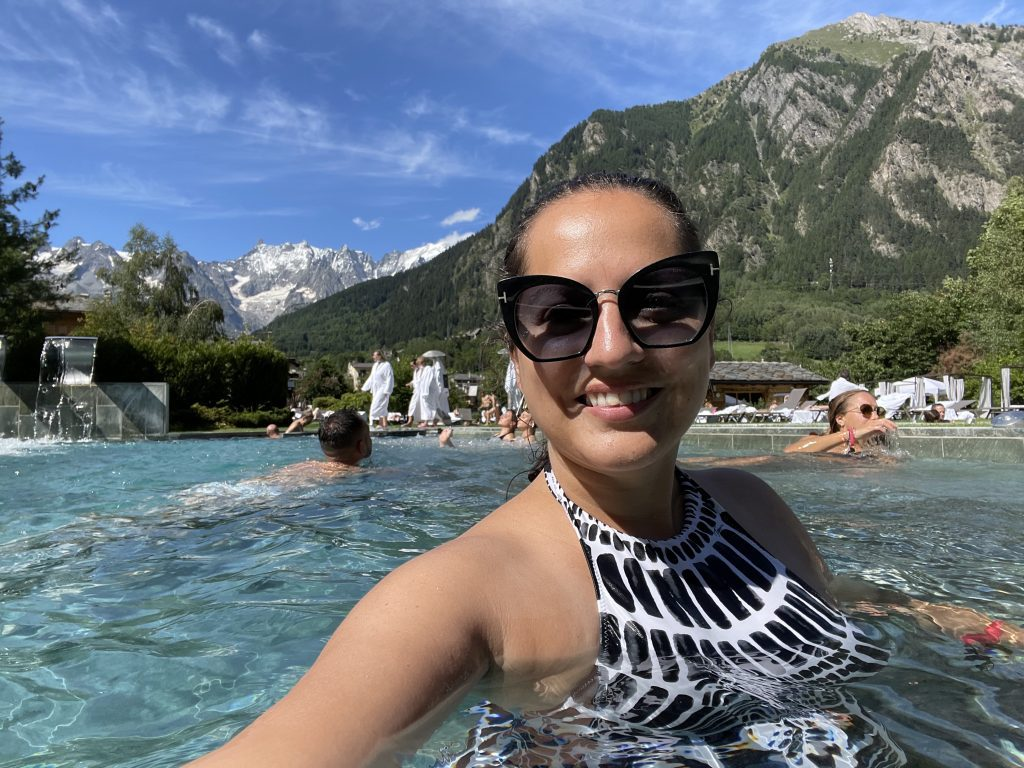 Kate takes a selfie and smiles in a black and white patterned bathing suit and sunglasses. She's in a pool and in the background you see green mountains, then taller snow-covered gray mountains.