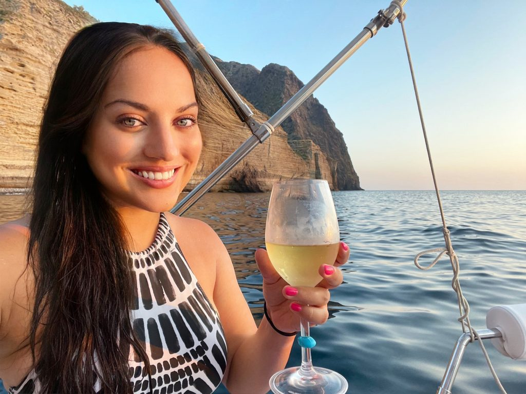Kate smiles and wears a black and white patterned bathing suit while sitting on a boat. She's holding a glass of white wine and behind her you see tall striped cliffs and blue water.