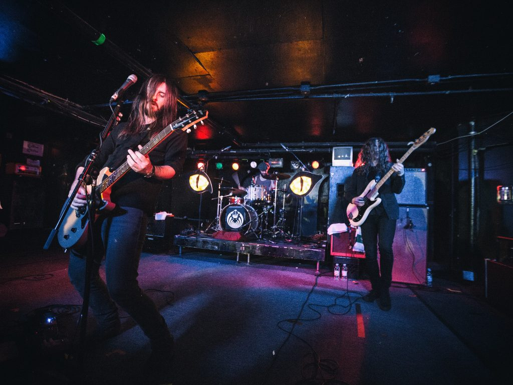 Two long-haired men in a band playing guitar on stage.