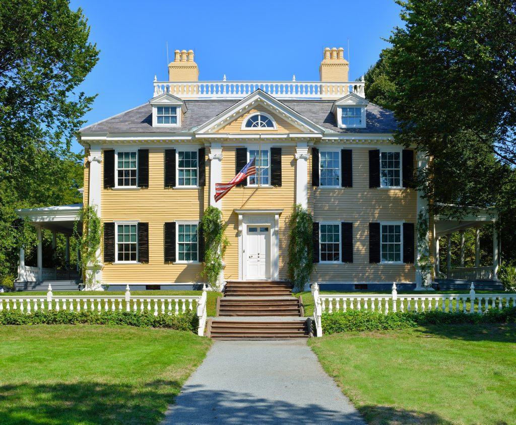 A yellow house with black shelters and an American flag waving from the front.