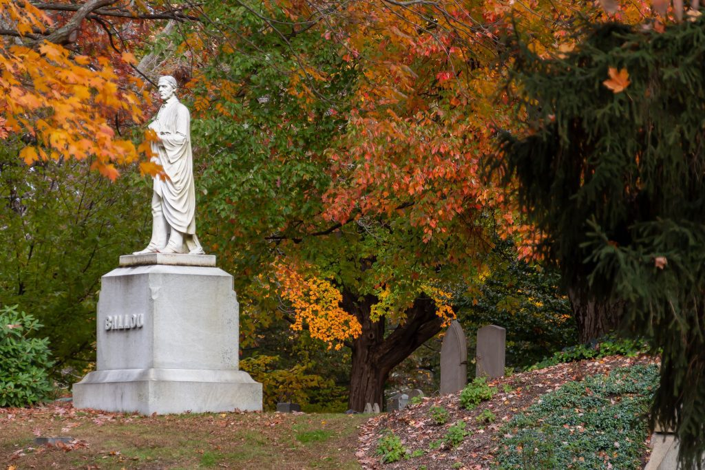 A white statue of a man on top of a gravestone in a cemetery, orange leaves behind it.