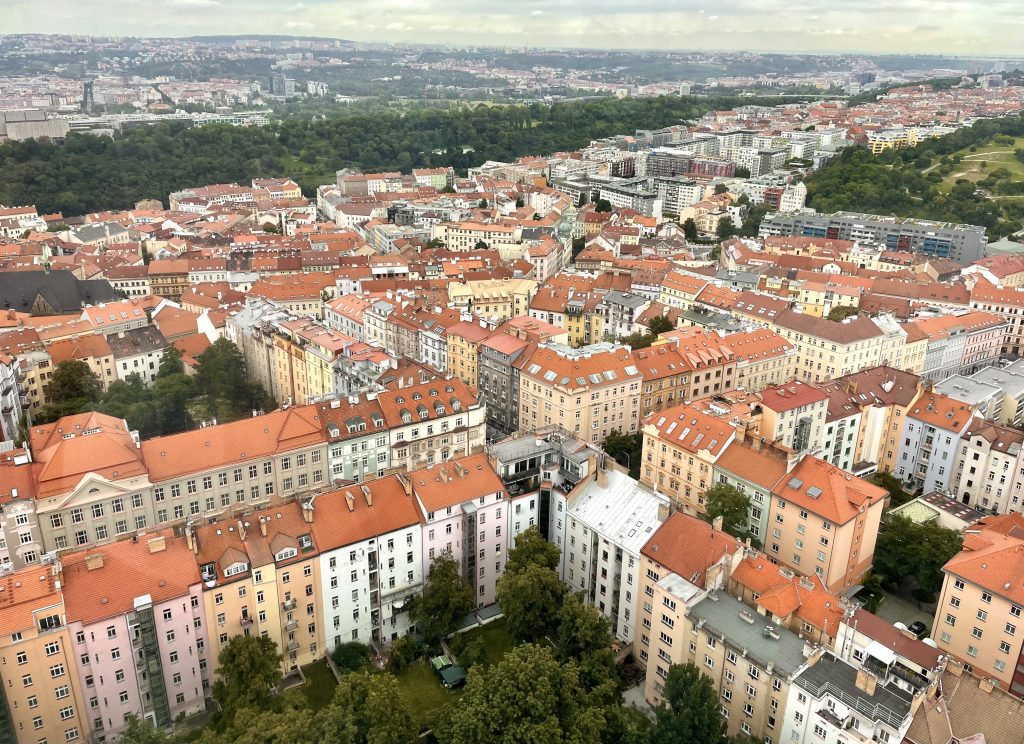 A view of Prague from the top of the TV tower: you see grids of pink, yellow, orange, and white-colored apartment buildings surrounding courtyards, all with orange roofs.