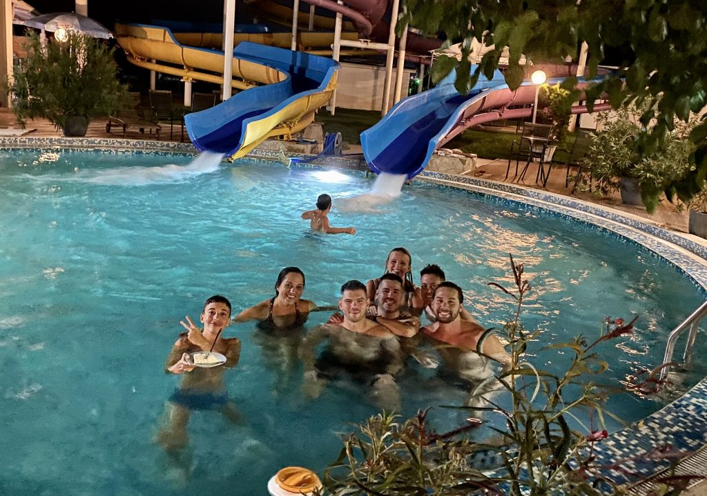 Kate and five of her friends, plus two teenage boys, in a pool into which two waterslides are feeding. One of the boys is eating a slice of cake in the pool!
