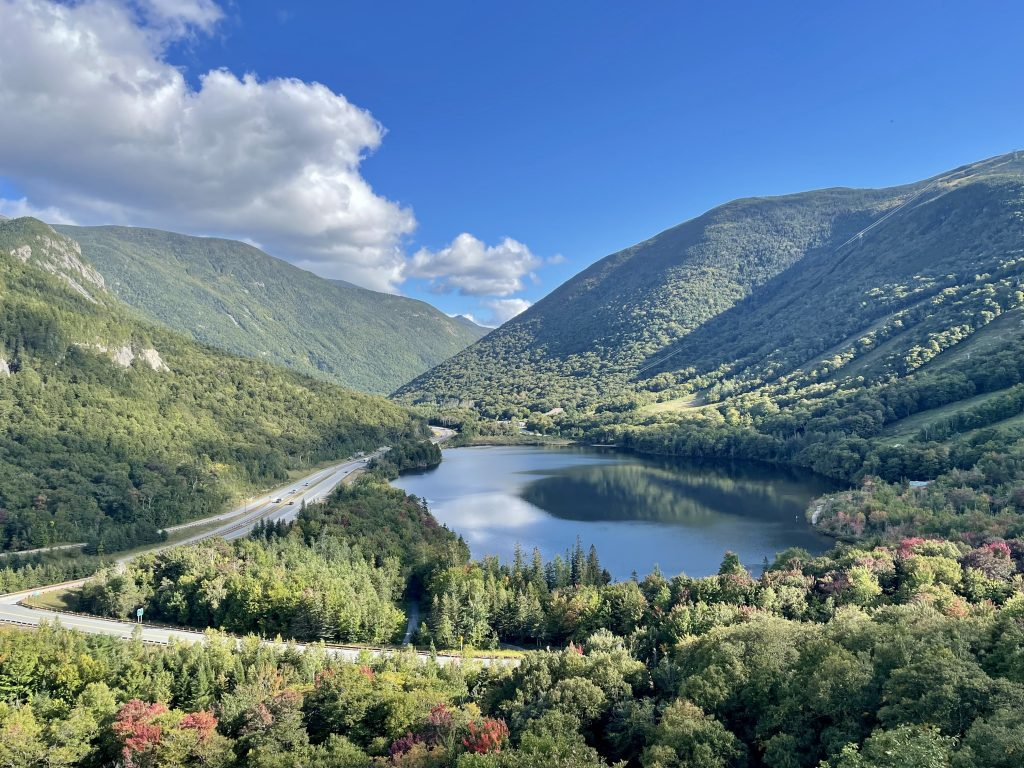 View through the middle of a valley surrounded by green mountains, a small highway snaking by the left side and a calm navy blue glassy lake in the middle. A few of the trees are starting to turn red.