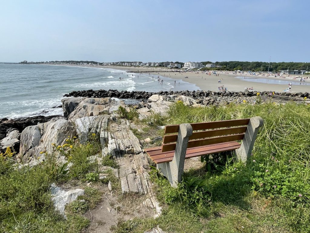 A weathered wooden and concrete bench placed among tall grasses on a rocky cliff overlooking a long beach in Rye, New Hampshire.