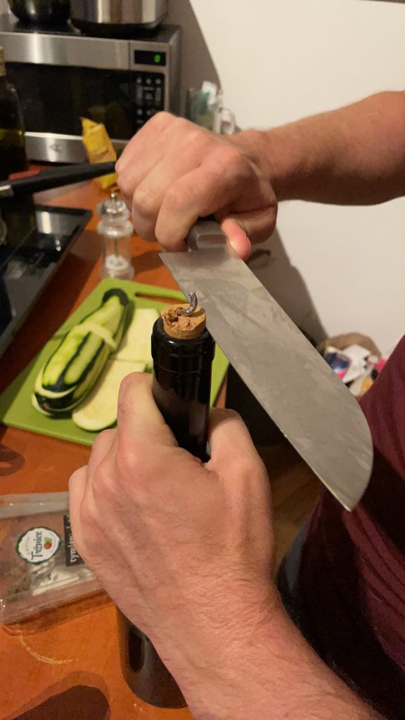 A wine bottle with the cork partway out, the metal spiral wine opener lodged in it. Charlie's hands are trying to cut the cork out with a giant butcher knife.