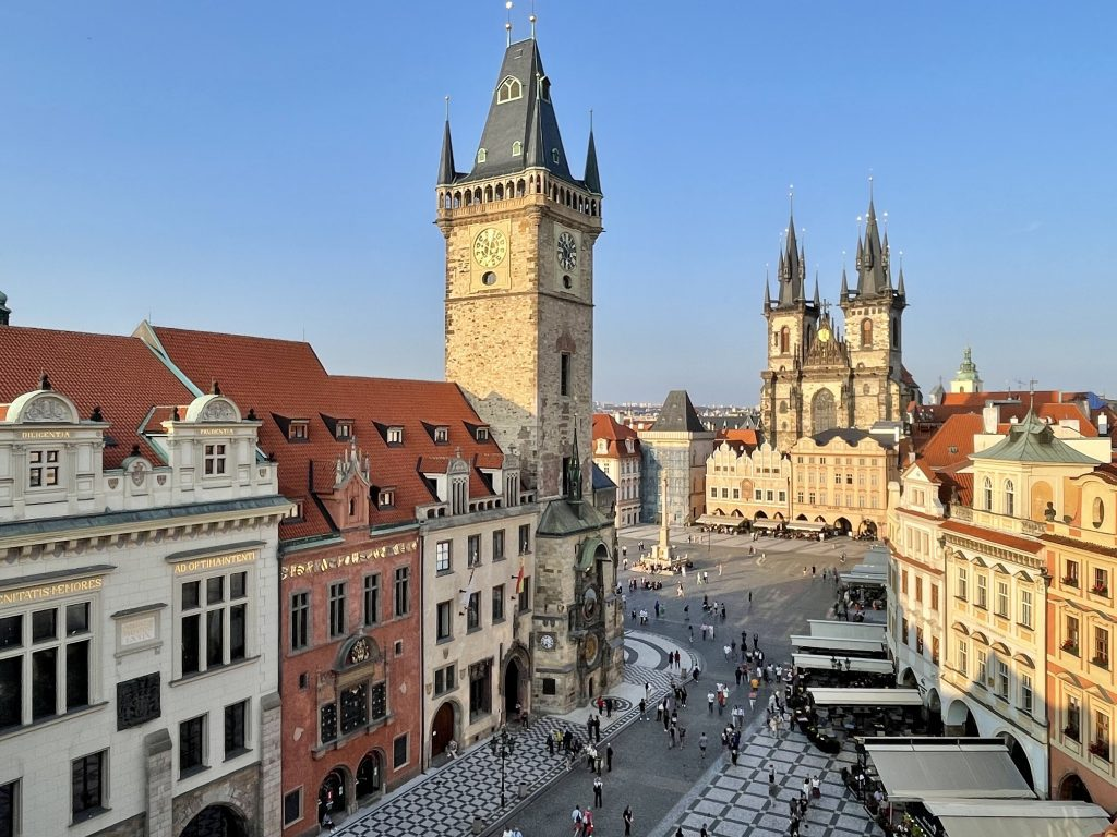 Prague's Old Town Square from above. You see spindly church towers, the Astronomical clock, and candy-colored crenellated buildings with gold decoration.